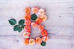 B, roses fleurissent l'alphabet d'isolement sur le fond en bois gris, configuration d'appartement Image stock