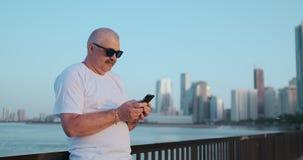 B?rtiger ?lterer Mann, der drau?en unter Verwendung des Smartphone steht Pensionierte m?nnliche Lesenachrichten, plaudernd mit se stock video footage