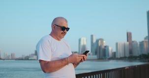 B?rtiger ?lterer Mann, der drau?en unter Verwendung des Smartphone steht Pensionierte m?nnliche Lesenachrichten, plaudernd mit se stock video