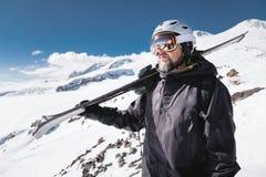 B?rtiger m?nnlicher Skifahrer des Nahaufnahme-Portr?ts gealtert gegen Hintergrund von Bergen Ein tragender Ski des erwachsenen Ma lizenzfreie stockfotos