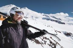 B?rtiger m?nnlicher Skifahrer des Nahaufnahme-Portr?ts gealtert gegen Hintergrund von Bergen Ein tragender Ski des erwachsenen Ma stockfoto
