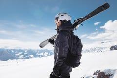 B?rtiger m?nnlicher Skifahrer des Nahaufnahme-Portr?ts gealtert gegen Hintergrund von Bergen Ein tragender Ski des erwachsenen Ma lizenzfreie stockfotografie