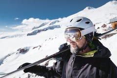 B?rtiger m?nnlicher Skifahrer des Nahaufnahme-Portr?ts gealtert gegen Hintergrund von Bergen Ein tragender Ski des erwachsenen Ma lizenzfreie stockbilder