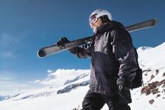 B?rtiger m?nnlicher Skifahrer des Nahaufnahme-Portr?ts gealtert gegen Hintergrund von Bergen Ein tragender Ski des erwachsenen Ma lizenzfreies stockfoto