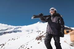 B?rtiger m?nnlicher Skifahrer des Portr?ts gealtert gegen Hintergrund des Schnee-mit einer Kappe bedeckten Kaukasus Ein tragender stockbilder