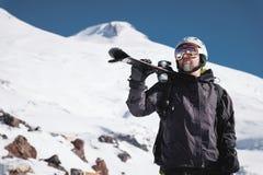 B?rtiger m?nnlicher Skifahrer des Portr?ts gealtert gegen Hintergrund des Schnee-mit einer Kappe bedeckten Kaukasus Ein tragender stockbild