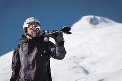 B?rtiger m?nnlicher Skifahrer des Portr?ts gealtert gegen Hintergrund des Schnee-mit einer Kappe bedeckten Kaukasus Ein tragender lizenzfreie stockfotografie