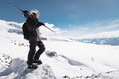B?rtiger m?nnlicher Skifahrer des Wachstums-Portr?ts gealtert gegen Hintergrund des Schnee-mit einer Kappe bedeckten Kaukasus Ein stockbilder