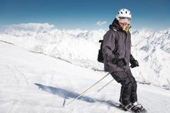 B?rtiger m?nnlicher Skifahrer in einem Sturzhelm und Bremsen einer Sturmhaube mit Schneepulver auf Skis vor dem hintergrund Schne lizenzfreies stockfoto