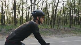 B?rtiger Radfahrer, der auf das Fahrrad tr?gt schwarze Sportausstattung, -sturzhelm und -gl?ser radelt Radfahrenkonzept stock footage