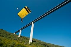 B.A.S.E. jumper descents under bridge. Royalty Free Stock Photos