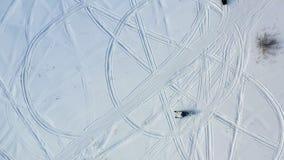 B?sta sikt av att rida sn?vesslor footage B?sta sikt av tv? sn?vesslor som k?r i cirkeln som l?mnar p? fotsp?r i sn? royaltyfri foto