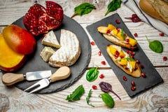 B?sta sikt av Bruschetta med den s?ta mango och ost p? en ljus tr?bakgrund sund mat royaltyfri foto