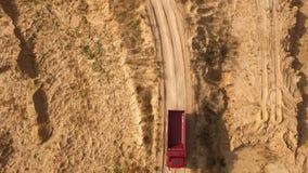 B?sta sikt av lastbilen som k?r p? den lantliga v?gen plats Dumperritter p? den torra gula villebr?dv?gen i sommar Tungt maskiner arkivfoto