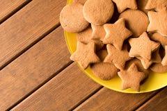 B?sta sikt av nytt gjorda kakor i en gul platta p? en tr?tabell Tomt avst?nd f?r text royaltyfri bild