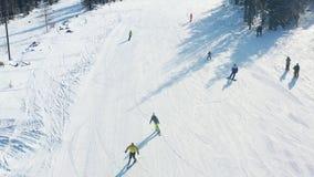 B?sta sikt av skid?kare och snowboarders som rider p? berget footage Skidar semesterorten med aktiv vilar p? skidar och snowboard royaltyfri bild