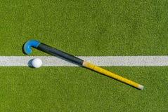 B?ton de hockey et boule de champ sur l'herbe verte photo libre de droits