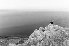 B&W απότομος βράχος πετρών συνεδρίασης φωτογράφων ατόμων επάνω από τη θάλασσα λιμνών Στοκ Φωτογραφίες