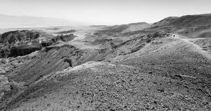 B&W backpacker walking desert mountains. Black and white tourist backpacker traveling walking desert mountain cliffs, Arava, negev desert, Israel Royalty Free Stock Images