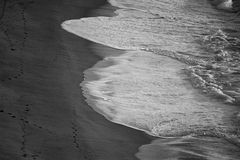 B&W beach from above. Black and white shot taken from a cliff looking down on the water washing over the sand Royalty Free Stock Photography