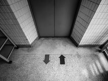 B&W The entrance of elevator. B&W Interior corridor view facing the entrance of elevator or lift doors with arrow symbol on the floor Royalty Free Stock Image