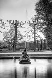 B&W fountain envisioning a girl sitting on top of a goose jets water into the air mid pond Royalty Free Stock Photo