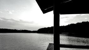B&W Lake from the Dock. Thus black and white rendition of a fiery sunset on the lake is viewed in the foreground from a covered wooden dock. Pulls the viewer Stock Photo
