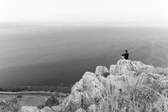 B&W man photographer sitting stone cliff above lake sea. Stock Photos