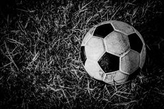 B&W old dirty ball on grass Royalty Free Stock Images