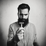 B/w portrait of brutal bearded man looking at vintage razor Royalty Free Stock Photography