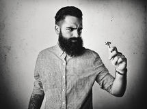 B/w portrait of a brutal bearded man looking at vintage shaver Stock Photos