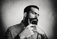 B/w portrait of a man grooming his beard with scissors Royalty Free Stock Photography