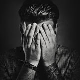 B/w portrait of a man hiding his face Royalty Free Stock Photography