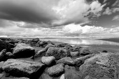 B&W of rocks by Pacific ocean. Stock Photo