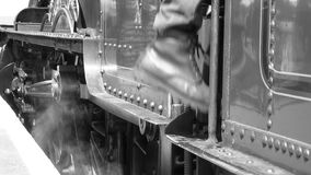 B&W shot as steam train driver climbs onto steam engine 4K. Black and white footage of steam train drivers legs going onto a steam engine 4K stock video