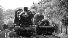 B&W shot of team train coming into station 4K. Steam train comes into station and filmed in old style shot black and white 4K stock video footage