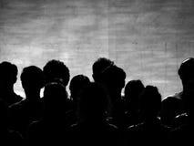 B&W : Silhouettes des personnes sous des lumières d'étape Photos stock