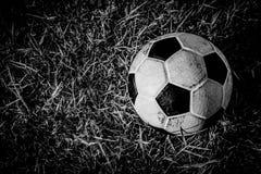 B&W stara brudna piłka na trawie Obrazy Royalty Free