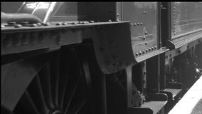 B&W steam engine low shot of wheels moving from stationary slowly forward 4K stock footage
