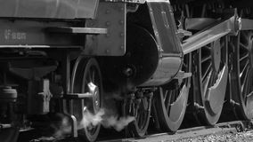 B&W steam engine moving slowly forward low shot 4K stock video