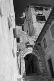 Street in Rovigno. Detail of a street with bricks and old walls and shades - converted in black and white for more drama - Rovigno, Croazia Royalty Free Stock Image