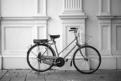 B&W vintage bicycle parked next to a white wall. Stock Photography