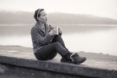 B&W of woman relaxing by lake. Stock Image