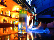 B52 flaming cocktail. A long trickle of alcohol is put on the bar and a bartender burns it. When cocktail catches fire, a person should drink it though a pipe Royalty Free Stock Image