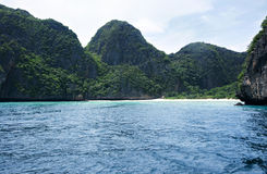 Baía branca tropical abandonada da praia da areia no meio-dia cercada por montanhas e pela água verdes do oceano do azul de turqu Imagem de Stock