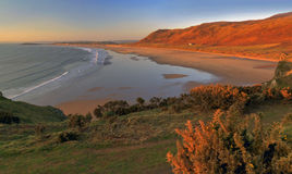 Baía de Rhossili do fulgor do por do sol Fotos de Stock Royalty Free
