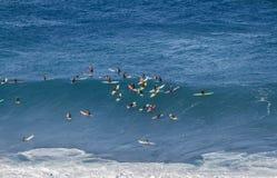 A baía Oahu Havaí de Waimea, grupo de A dos surfistas espera uma onda para surfar Imagens de Stock