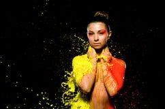 Bañan a una muchacha en pintura amarilla en un lado y pintura anaranjada en el otro Foto de archivo libre de regalías