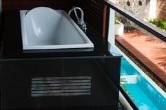 Bañera blanca en el balcón con la opinión de la piscina abajo Imágenes de archivo libres de regalías