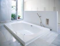 Bañera blanca moderna del cuarto de baño de la casa con el tragaluz del patio fotografía de archivo